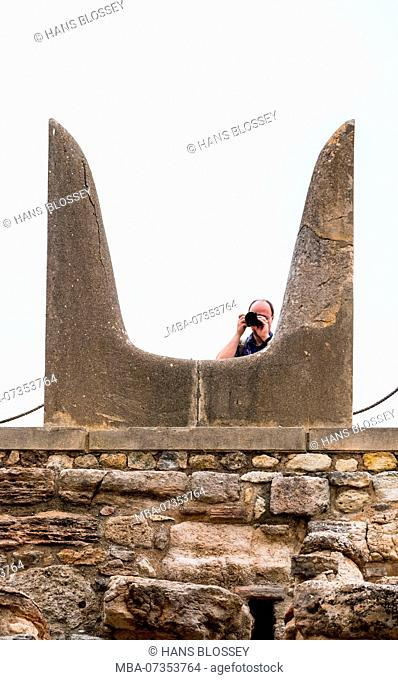 Consecration horns, sacred bull horns with photographing tourist, symbol of the sacred bull of stone, parts of the Minoan temple complex of Knossos