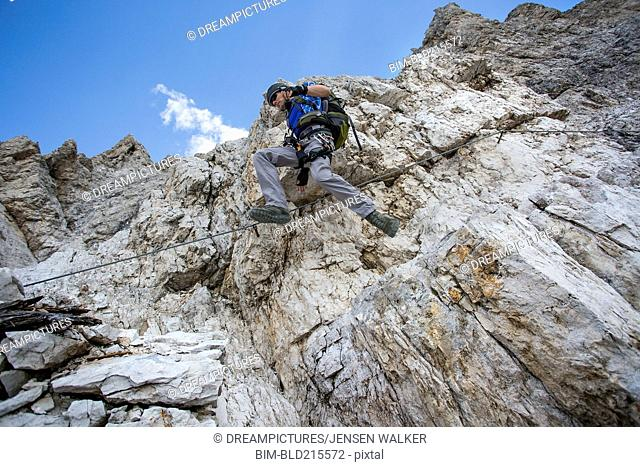 Low angle view of Caucasian climber scaling remote mountain slope