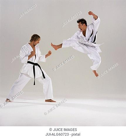 Two men in karate competition, one in mid-air