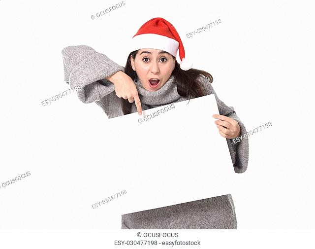 young attractive Hispanic woman wearing Santa Claus Christmas hat and winter jumper holding and pointing blank billboard or placard sign as copy space adding...