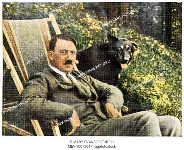 ADOLF HITLER (1889-1945), relaxing in a deckchair at Berchtesgaden, with a black dog at his side