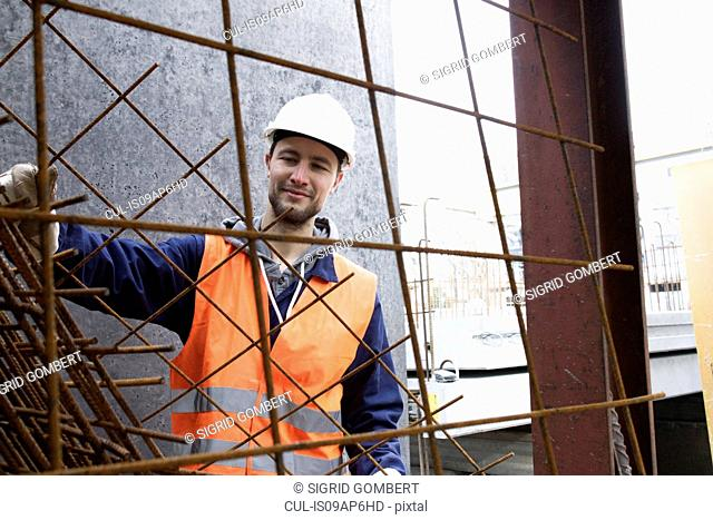 Portrait of factory worker selecting steel mesh at concrete reinforcement factory