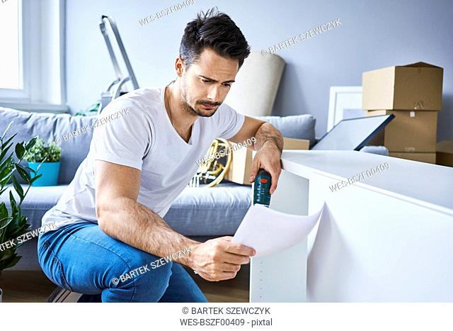 Man reading instructions while assembling furniture in new apartment