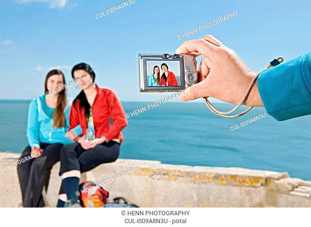 Young female friends having their photograph taken at coast