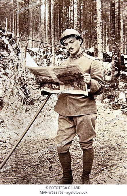 LETTURA Militare legge la Domenica del Corriere, periodico illustrato, in un bosco durante una tregua. Italia 1915 - 1918