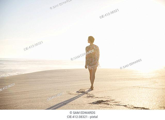 Pensive, serene woman walking on sunny summer beach