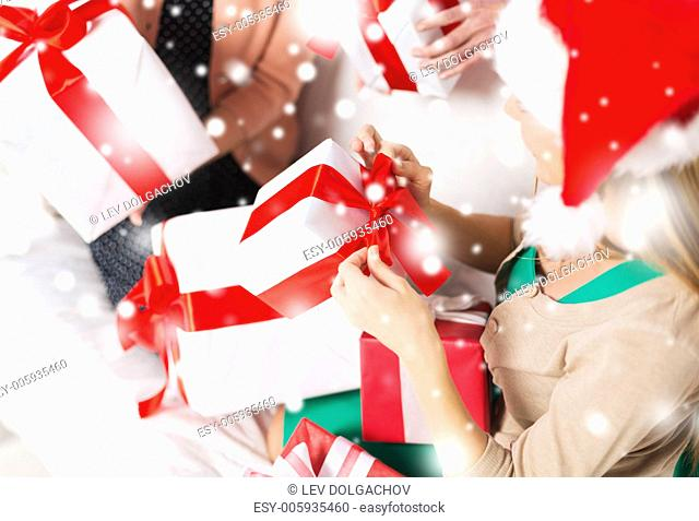 christmas, x-mas, happiness, winter and people concept - three women in santa helper hats holding many gift boxes