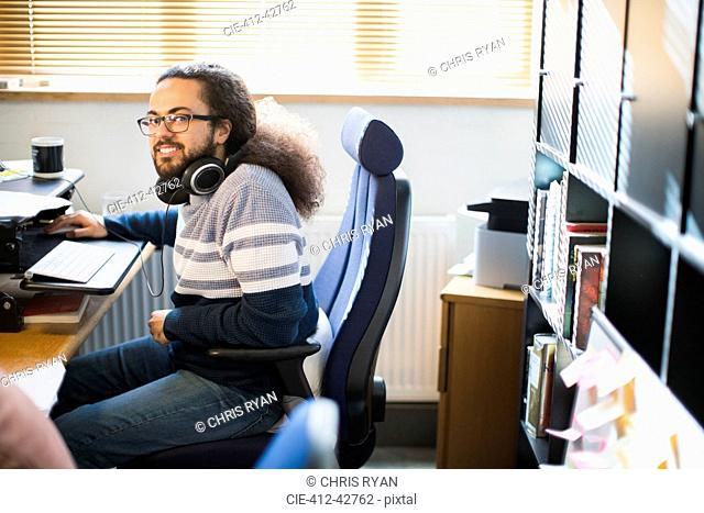 Portrait smiling, confident creative businessman with headphones working in office