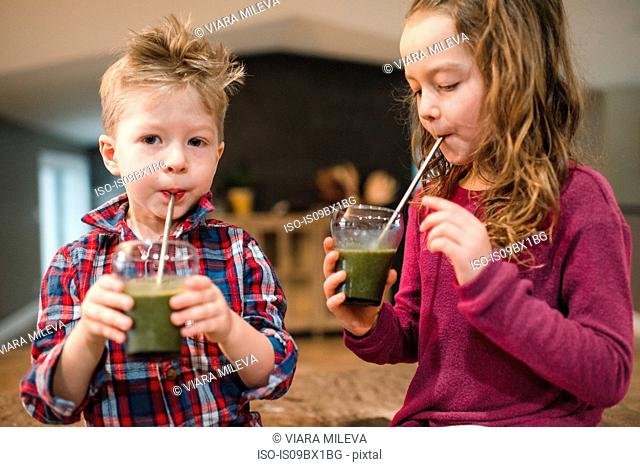 Children drinking green juice with straw