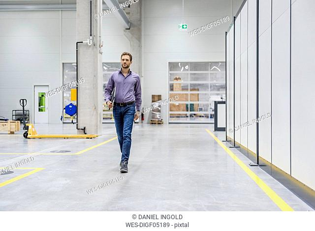 Businessman walking in factory workshop, carrying digital tablet
