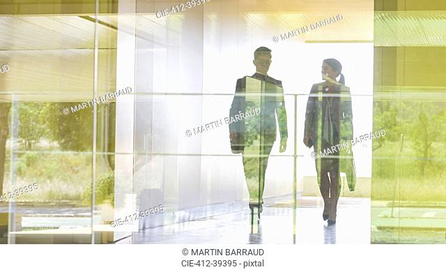 Silhouette businessman and businesswoman walking in modern office corridor