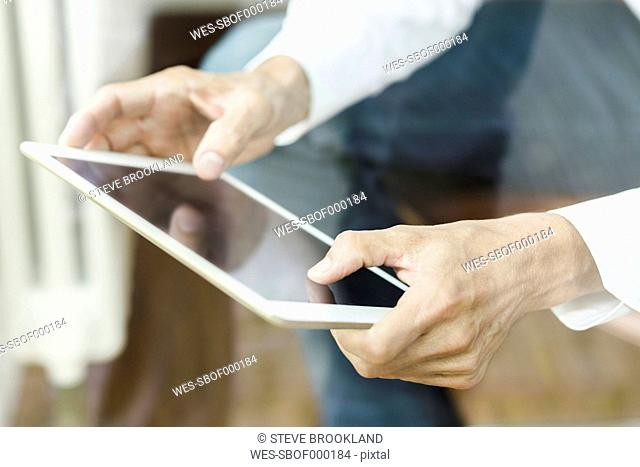 Hands of man using tablet, close-up
