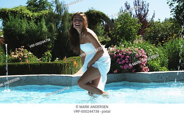 SLO MO MS Smiling teenage girl (16-17) playing in fountain in summer garden, Lehi, Utah, USA