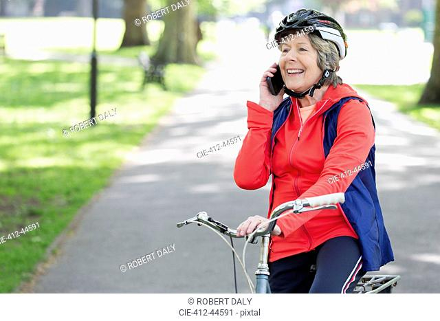 Active senior woman talking on cell phone on bike in park