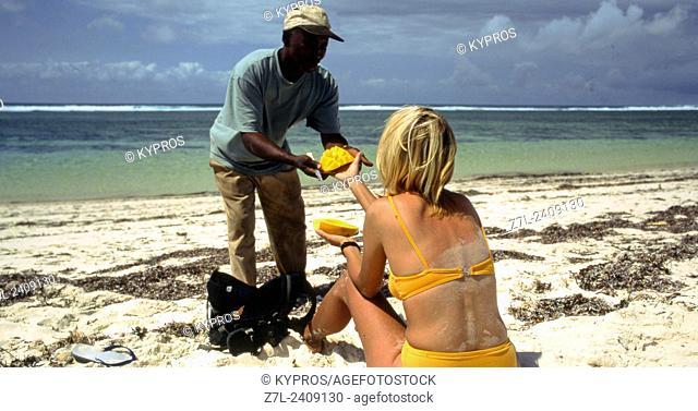 Young Caucasian Woman Wearing Biking Buying Fruit From African Man - Mombasa Beach. Kenya