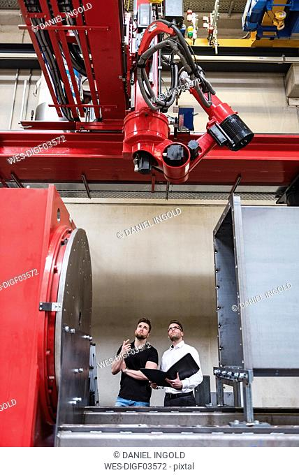 Two men with folder looking at machine on factory shop floor