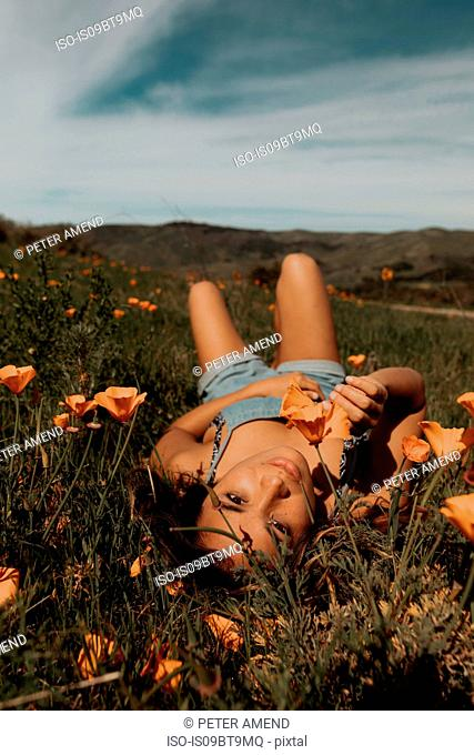 Young woman lying in field of wildflowers, portrait, Jalama, California, USA