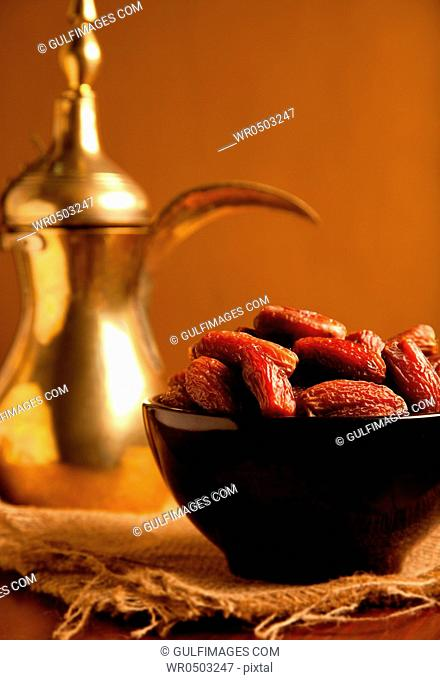 Bowl of dates and teapot on top of a native place mat