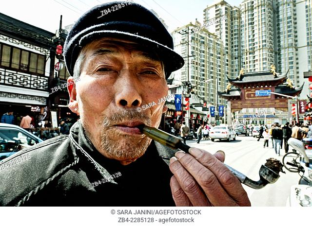 14ef307b9 A man smoking in a traditional tobacco pipe (Chinese tobacco pipes are  generally composed of