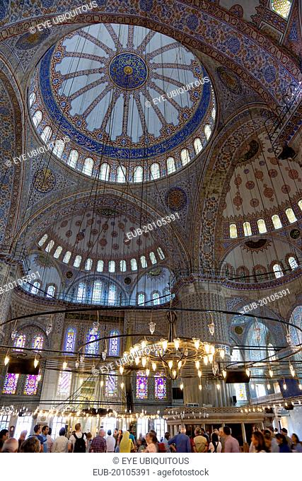 Sultanahmet Camii The Blue Mosque interior with sightseeing tourists by a chandelier below the decorated domes with stained glass windows beyond