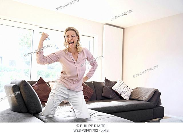 Portrait of exuberant woman posing on couch at home