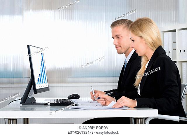 Young businessman and businesswoman analyzing graph on computer screen at desk in office