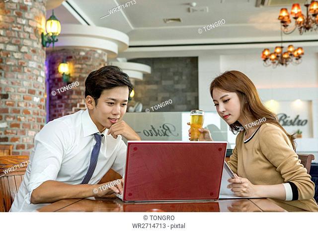 Businessman and businesswoman sharing a notebook computer