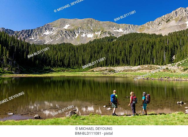 Hikers admiring still lake in rural landscape