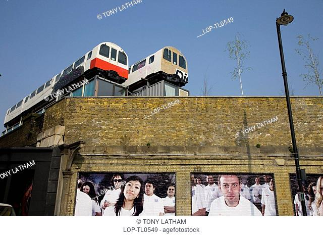 England, London, Shoreditch, Looking up to two tube carriages being used as offices on the top of a building in East London