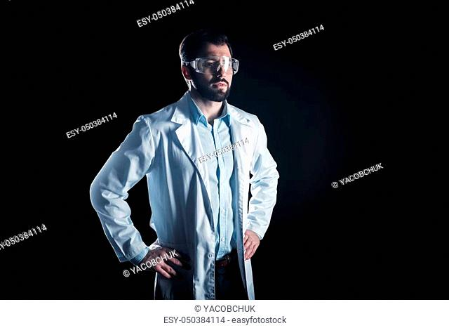 My inventions. Smart confident male scientist standing and looking in front of him while thinking about his inventions