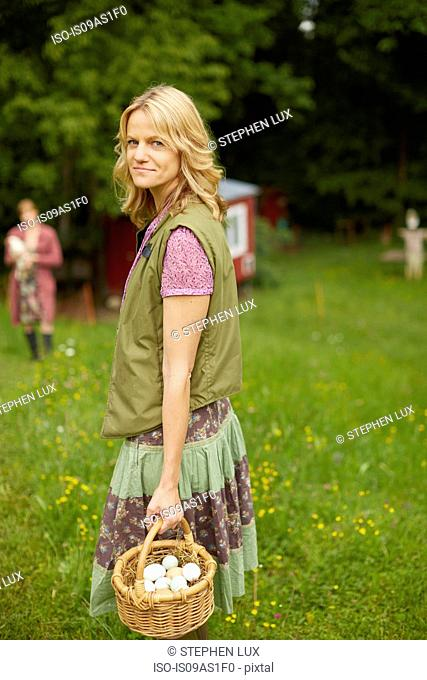 Portrait of woman in field holding basket of free range eggs