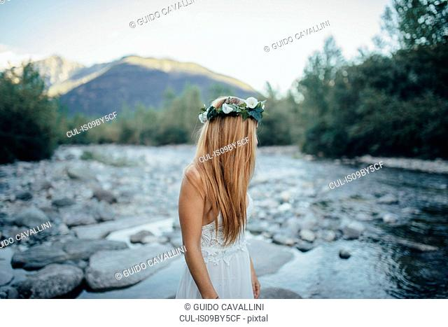 Woman in white dress looking back at river, Orta, Piemonte, Italy