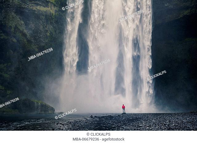 Southern Iceland. Man stands below the Skogafoss waterfall