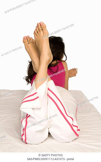 Woman lying on the bed and holding a remote control