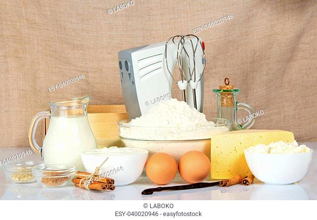 Mixer, sieve and products for baking, against a canvas