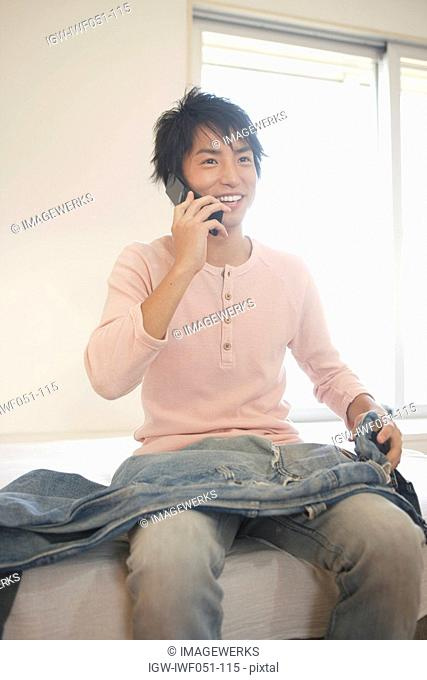 Young man with jeans and using mobile phone, smiling