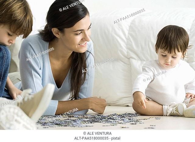 Mother and two children putting together jigsaw puzzle