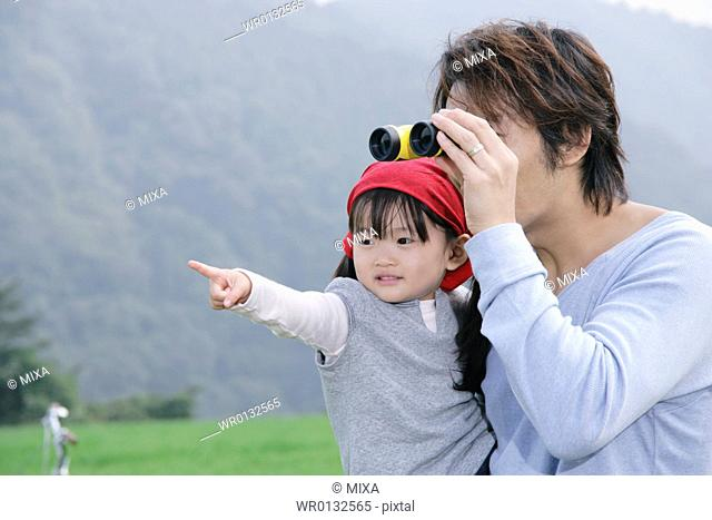 Father and daughter using binoculars
