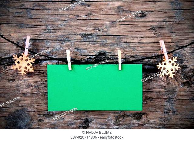 Empty Green Label with Snowflakes on a Line on Wood