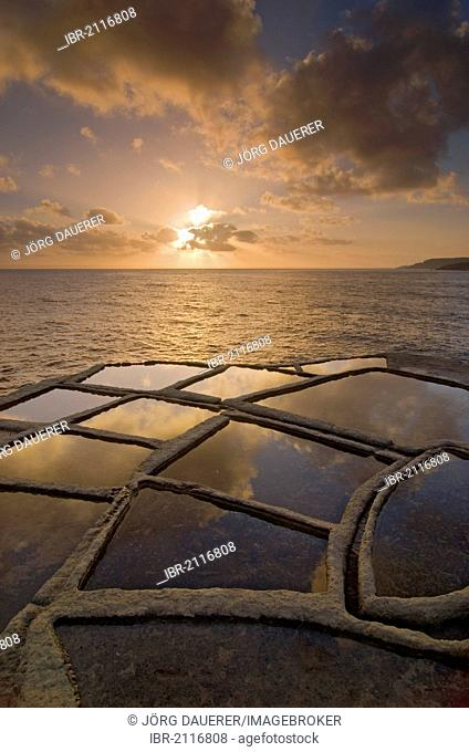 Sunrise and clouds above the typical salt pans or salterns, Qbajjar, near Marsalforn, northern coast of Gozo, Malta, Europe