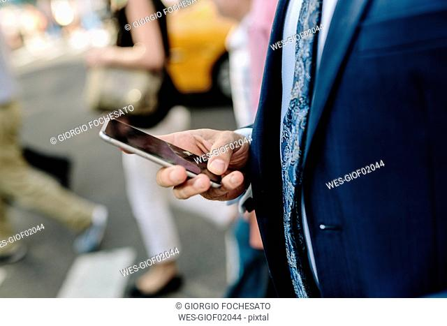 Handsome businessman walking in Manhattan, using mobile phone