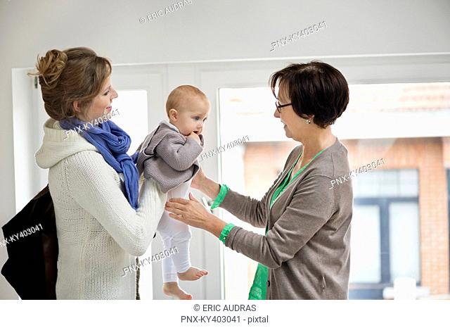 Woman giving her daughter to nanny