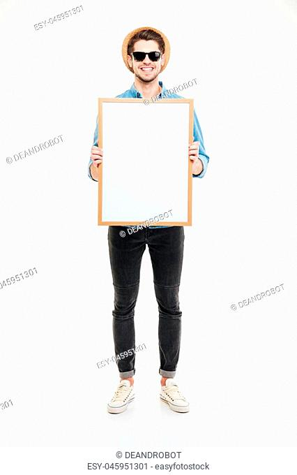 Full length of young man in hat and sunglasses holding blank whiteboard