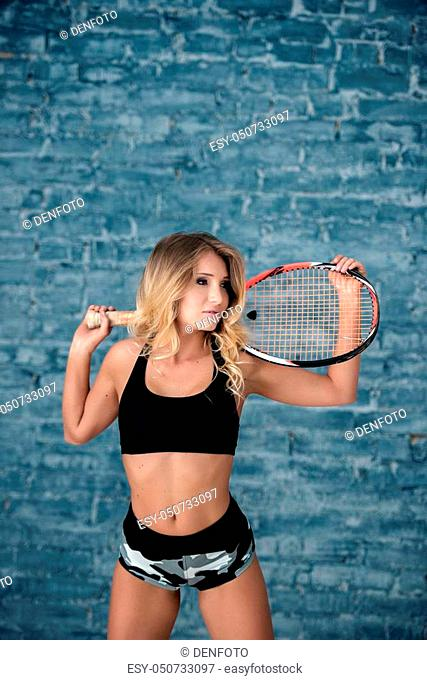 Portrait of a beautiful girl girl with a racket, a gray brick wall background
