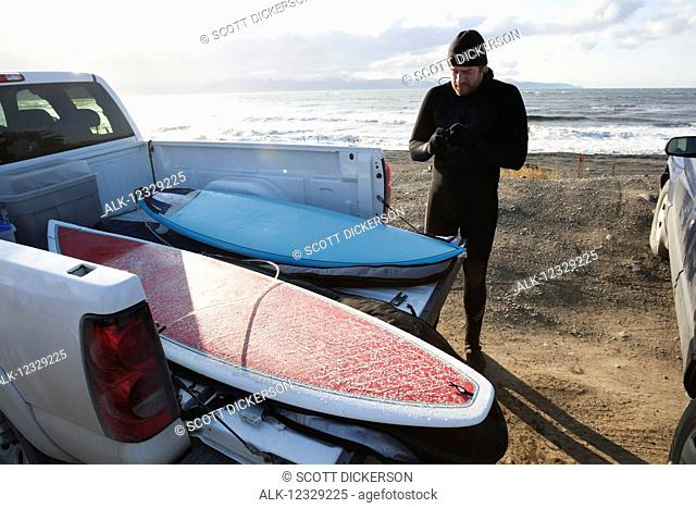Surfer preparing gear next to a truck with surfboards, Southeast Alaska; Yakutat, Alaska, United States of America