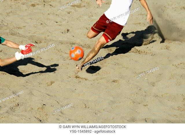 players in action at a beach soccer tournament