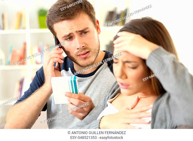 Man helping his ill wife calling doctor on phone sitting on a sofa in a house interior