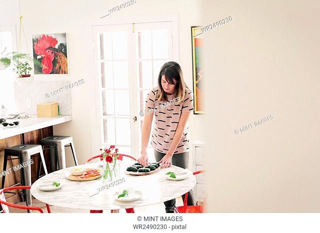 A woman laying a table for lunch