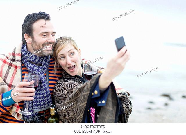 Couple on beach, drinking wine, taking self portrait using smartphone