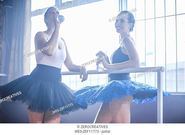 Two ballet dancers having a break in class